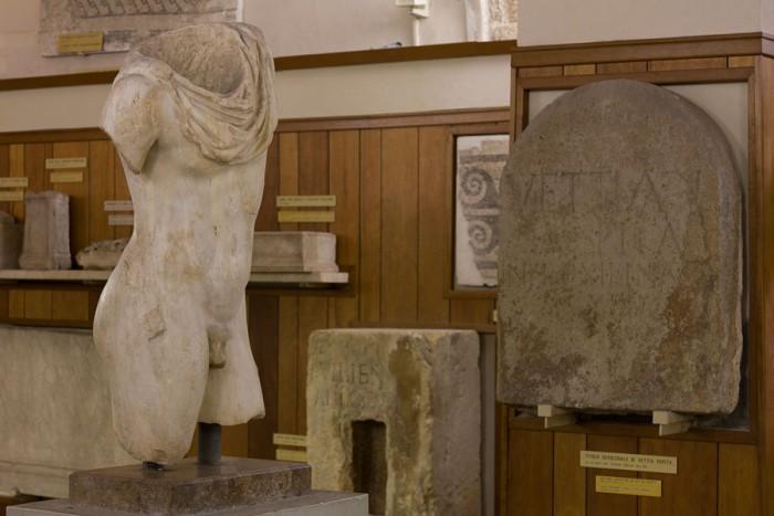 Torso di giovinetto e iscrizione sepolcrale a Vettia Hospita. Sullo sfondo, urne sepolcrali e un frammento di mosaico pavimentale romano.
