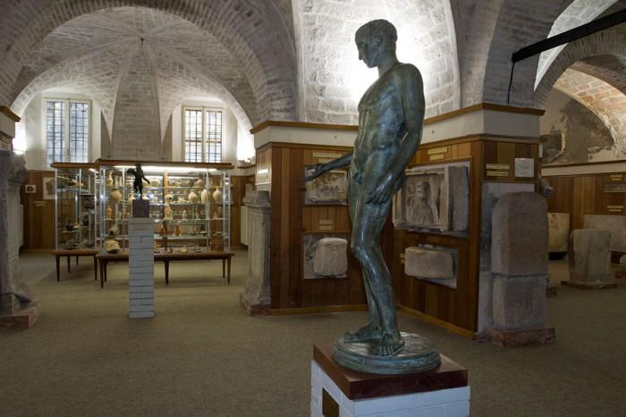 """Copia di statua in bronzo denominata """"Idolino di Pesaro"""". Sullo sfondo, Eros-Hypnos e bassorilievi di età romana."""